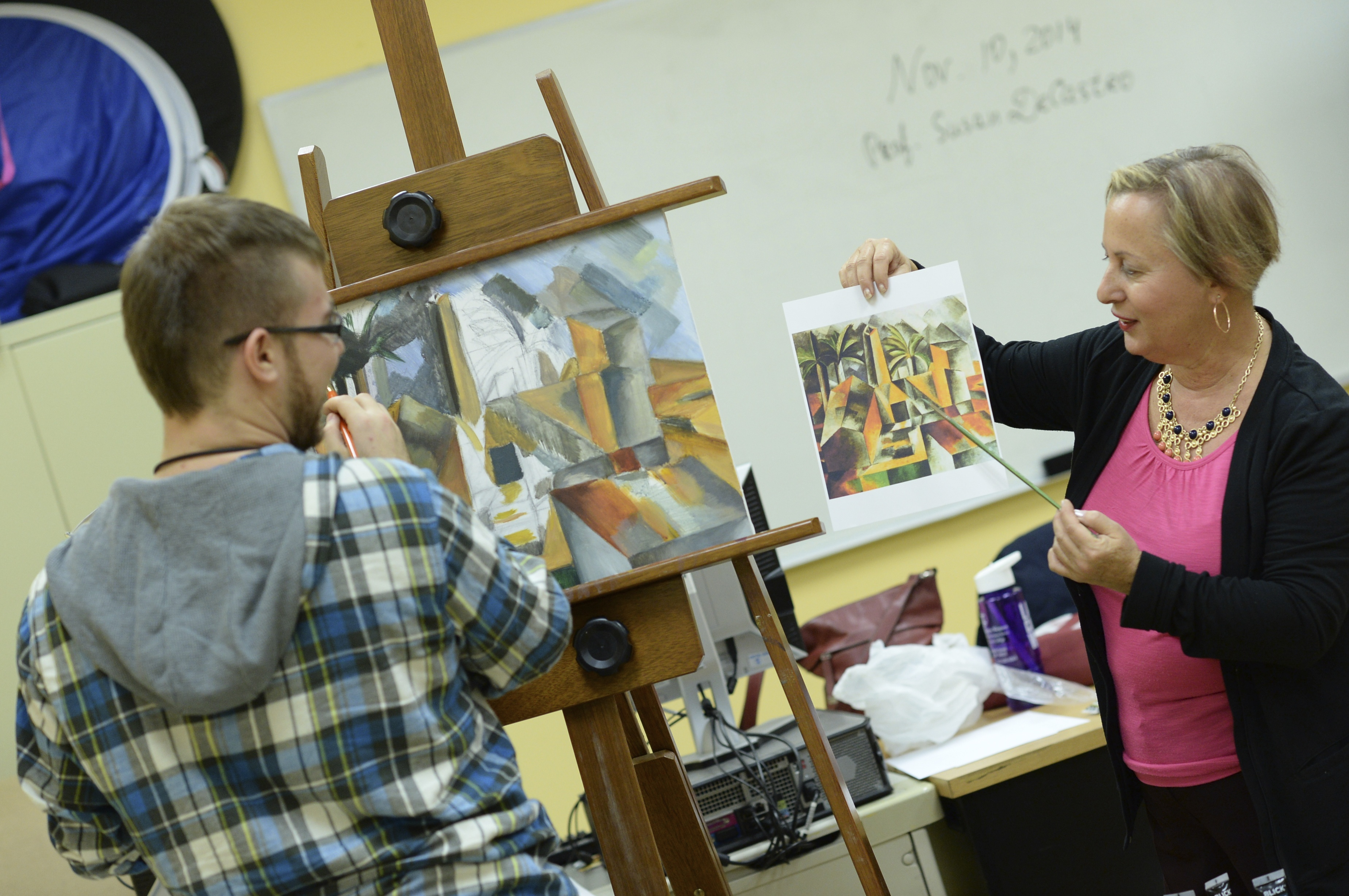 Professor Susan De Castro, holding up a print of a Picasso cubist painting, helps one of her students during class. The student is standing in front of an easel, working on his own cubist painting.