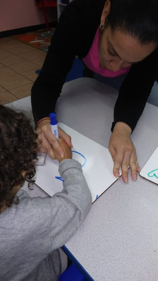 Angela Velez,a NYSCAS alumna, is pictured working with a student in her Bronx classroom.